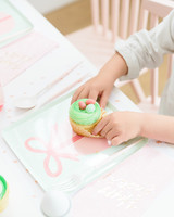 kid unwrapping green frosting easter cupcake