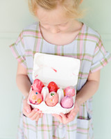 kid holding 6 decorated easter eggs