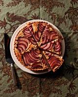 poached-pear frangipane tart on decorative green table cloth