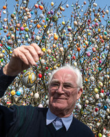 volker kraft holding up egg by decorated apple tree