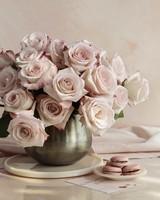 pink roses in vase next to macarons