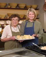martha stewart and another woman holding baked goods in kitchen