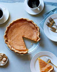 classic pumpkin pie on blue table with coffee