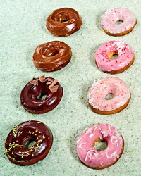 rows of doughnuts on green countertop