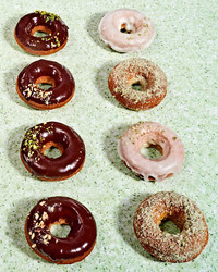 rows of doughnuts on green countertop with vegan and pumpkin flavors