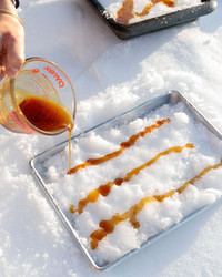 making maple taffy by pouring syrup on snow