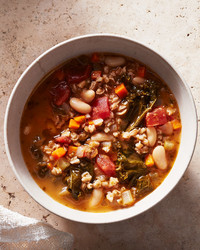kale white bean and farro soup served in a white bowl