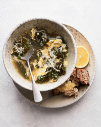 stracciatella soup with kale and lemon served in grey bowl with bread and lemon on the side