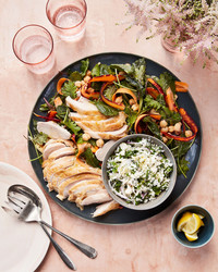 roasted chicken with cauliflower tabbouleh served on a black plate