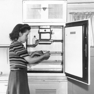 Woman using an old refrigerator