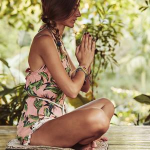 woman meditating in tropical garden
