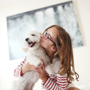 Young girl giving her pet dog a kiss
