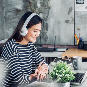 businesswoman working next to desk plant