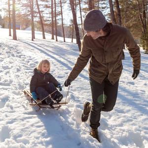 man pulls child on wooden sled across snow