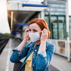 woman wearing mask waiting for train