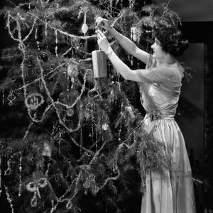 woman decorating a Christmas tree