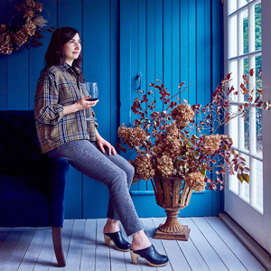 woman looks out window while drinking glass of wine in blue room