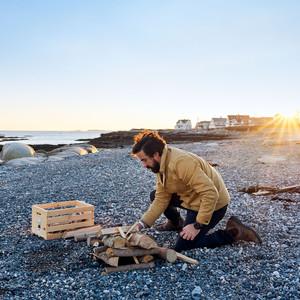 man setting up bon fire on beach