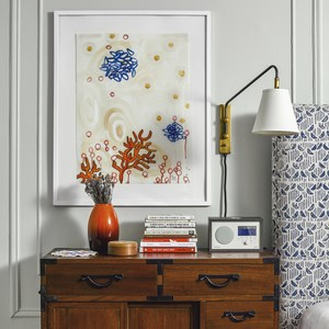 Colorful art hangs over a nightstand