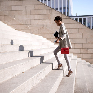 woman dressed in neutral attire wearing red purse walking up stairs