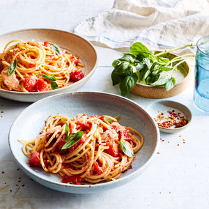 spaghetti and no-cook tomato-tuna sauce topped with basil leaves