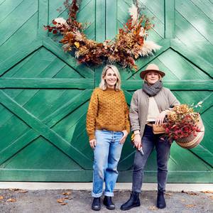 women stand beneath wreath on green barn door