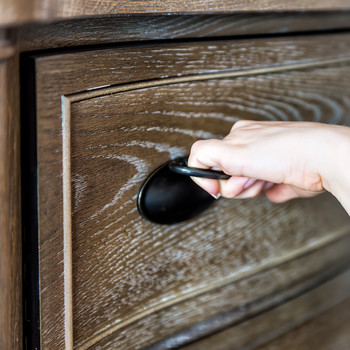 hand pulling open wooden dresser drawer