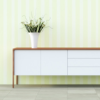 A sideboard and plant against green and white striped wallpaper.