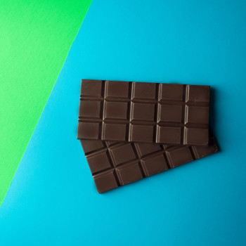 A bar of dark chocolate unwrapped, on a blue and green geometric background.