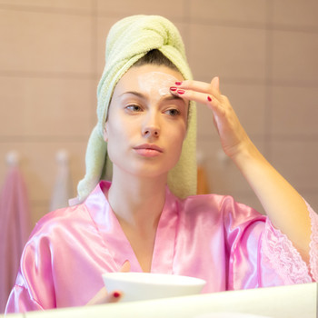 A woman applies face cream while looking in a mirror.