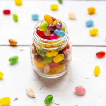 glass jar of jelly beans with many on table
