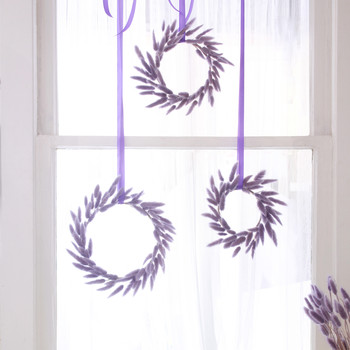 a trio of bunny tail wreaths in the window