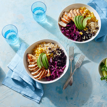 burrito bowl with avocados corn rice chiken beans and cabbage on blue table