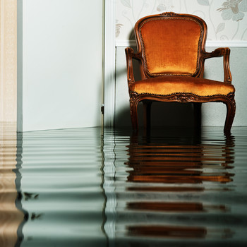 flooded living room with a chair in a home