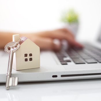 person typing on laptop keyboard with house and key keychain
