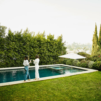 two people holding wine glasses standing by outdoor pool