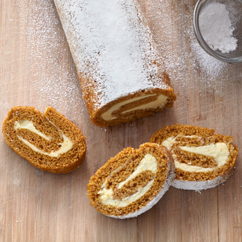 sliced pumpkin roll and sifter with powdered sugar