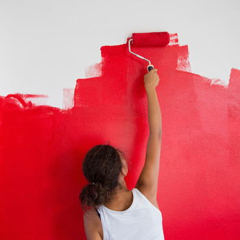 girl painting red wall with paint roller