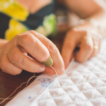 woman fixing quilt hem
