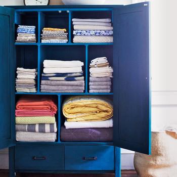 blue armoire storing linens