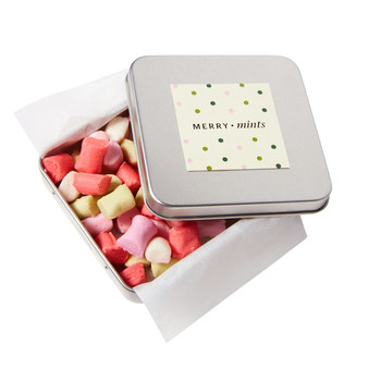 red pink and yellow butter mints in a tin box