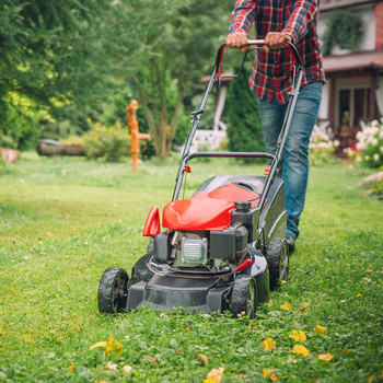 person mowing with push lawnmower
