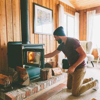 man stoking fire in cabin