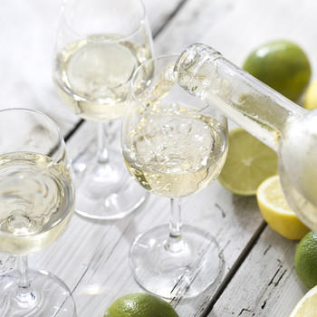 wine on table with lemons and limes