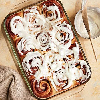 cinnamon rolls in glass pan with bowl of frosting