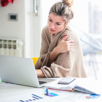 Cold Woman Sitting in Office Wrapped in Blanket