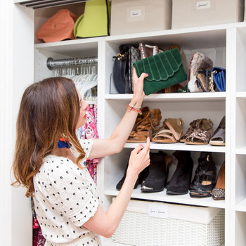 woman looking at green clutch on shelf with bags and shoes