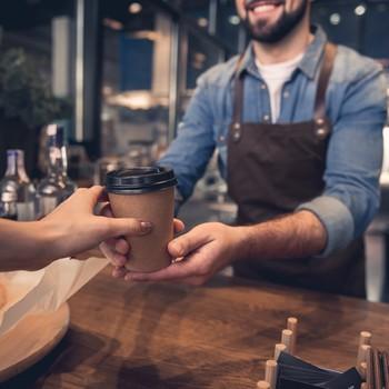 Barista handing woman a coffee cup