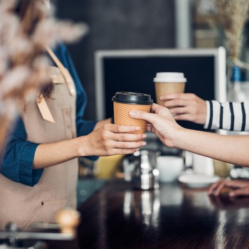 Barista handing cup of coffee to costumer