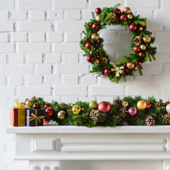festive holiday wreath above fireplace decorated with garland and gift boxes